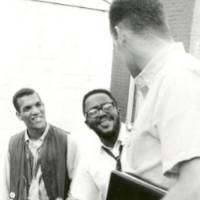 Three young black men looking at each other and smiling, the man in the foreground is turned away from the camera